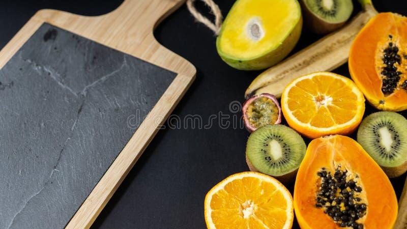 En uppsättning av frukter som klipps i halva, papaya, apelsin, banan, kiwi, mango fotografering för bildbyråer