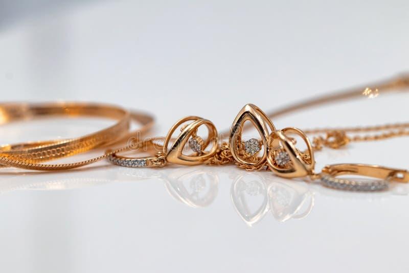 En uppsättning av guld- örhängen och hängear i form av droppar arkivfoton