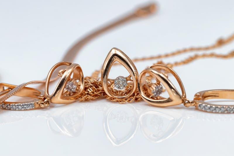 En uppsättning av guld- örhängen och hängear i form av droppar arkivfoto