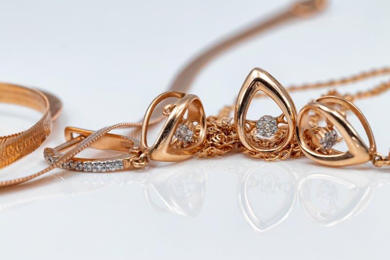 En uppsättning av guld- örhängen och hängear i form av droppar royaltyfria bilder