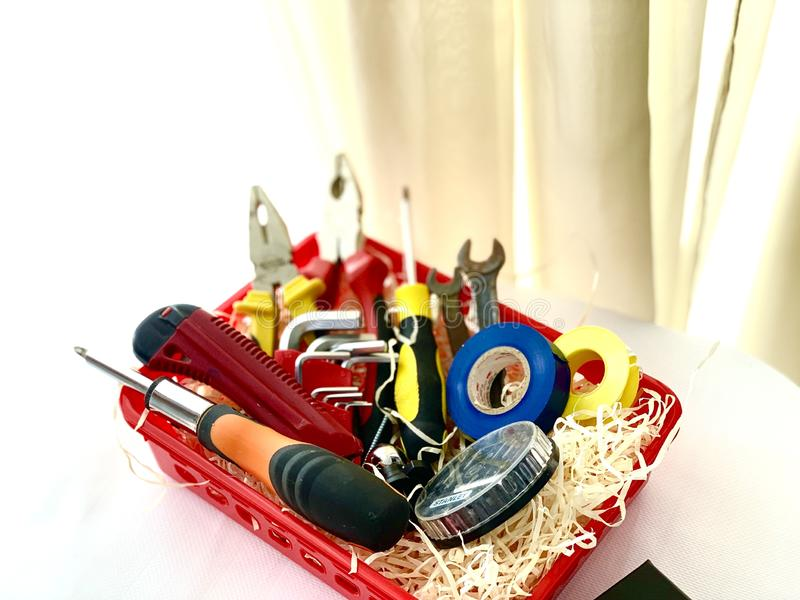 En uppsättning av hjälpmedel för reparation, plattång, skruvmejsel, elektriskt band, skiftnyckel R?d ask p? en vit bakgrund royaltyfria foton