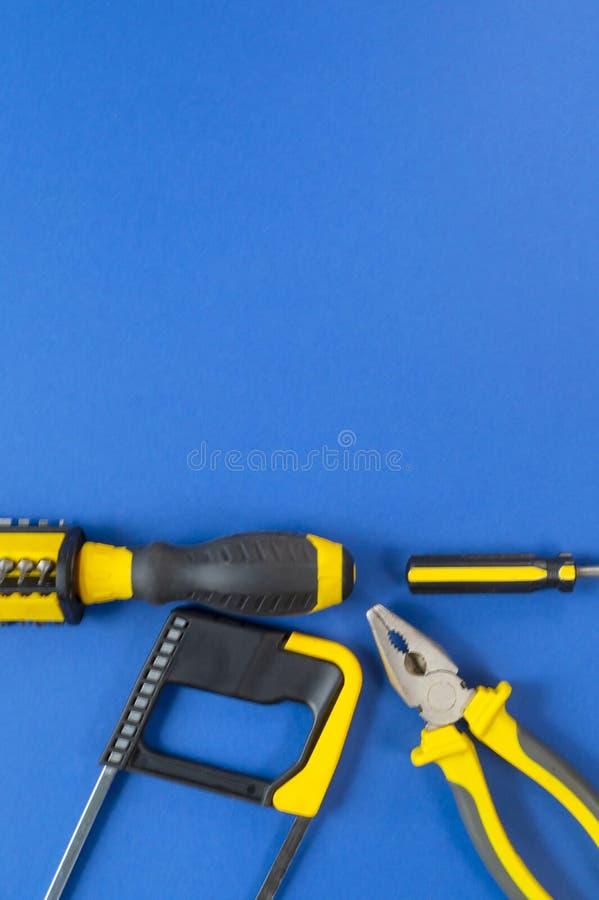 En uppsättning av hjälpmedel för reparation som isoleras på en blå bakgrund royaltyfri fotografi