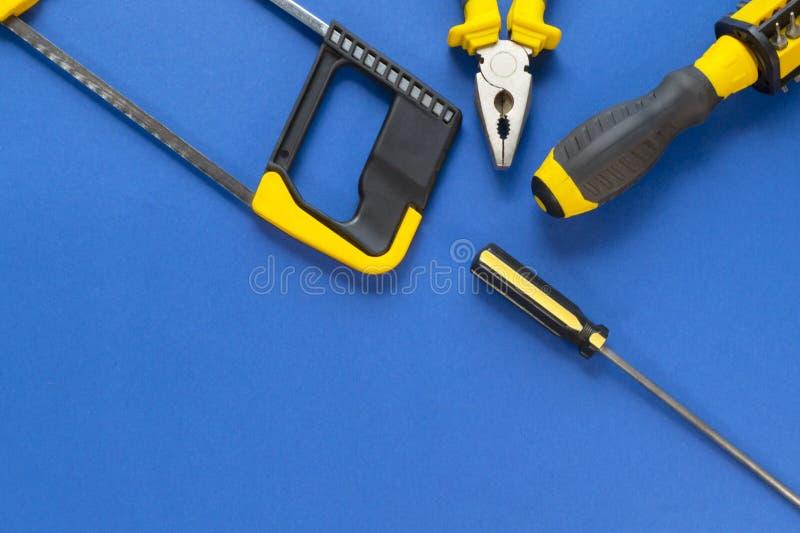 En uppsättning av hjälpmedel för reparation som isoleras på en blå bakgrund arkivbild