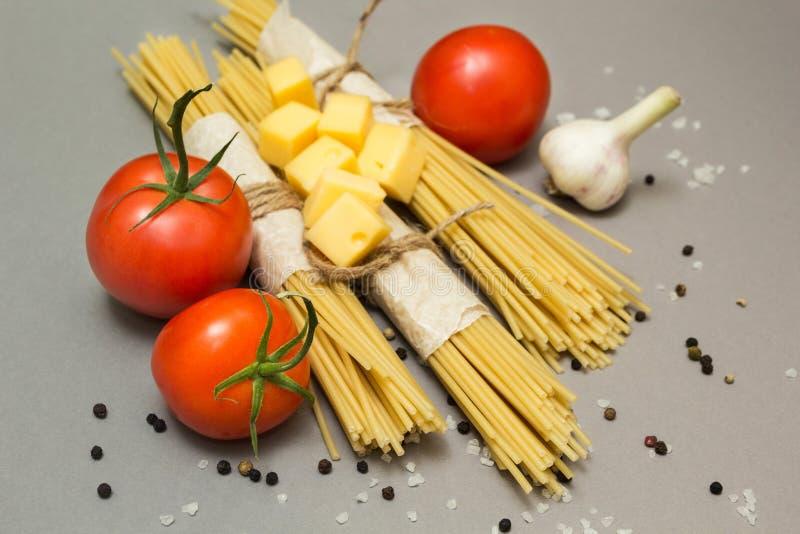 En uppsättning av ingredienser för att laga mat pasta på en grå bakgrund arkivfoton