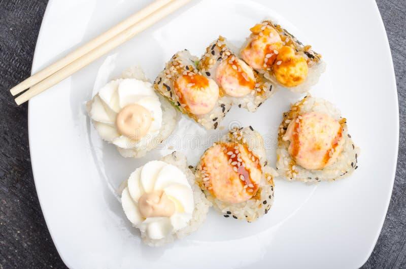 En uppsättning av klippta japanska sushirullar och pinnar på en vit plattacloseup royaltyfria foton