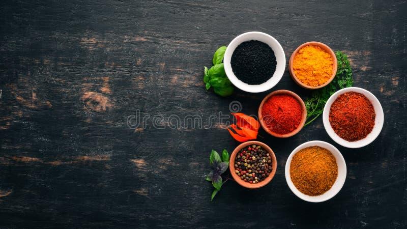 En uppsättning av kryddor och örter Indisk kokkonst Peppra, salta, paprika, basilika, gurkmeja På en svart träsvart tavla arkivfoton