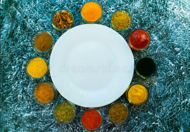 En uppsättning av kryddor och såser lade ut runt om en vit tom platta Indisk kokkonst pepprar, saltar, paprika, curry, basilika,  royaltyfri foto
