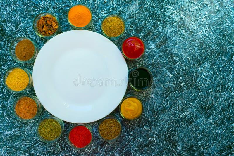 En uppsättning av kryddor och såser lade ut runt om en vit tom platta Indisk kokkonst pepprar, saltar, paprika, curry, basilika,  arkivbild
