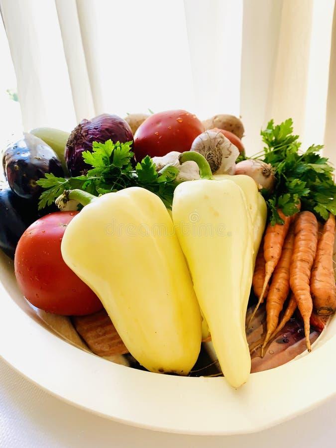 En uppsättning av naturliga grönsaker på ett uppläggningsfat Peppar morötter, potatisar, gräsplaner, aubergine, lök, vitlök Vit b royaltyfri bild