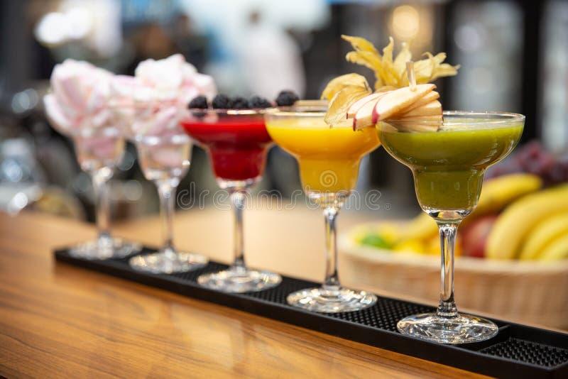 En uppsättning av olika kulöra smoothies i exponeringsglas på träbakgrund sund mat royaltyfri fotografi