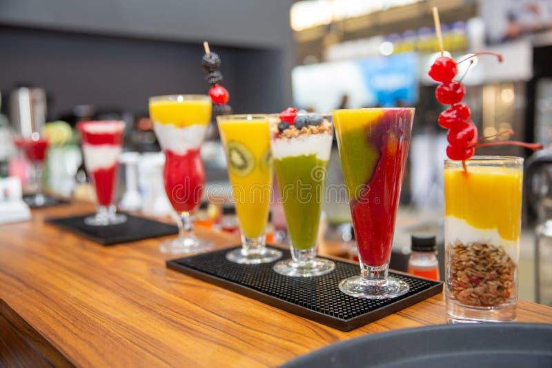 En uppsättning av olika kulöra smoothies i exponeringsglas på träbakgrund sund mat arkivbilder