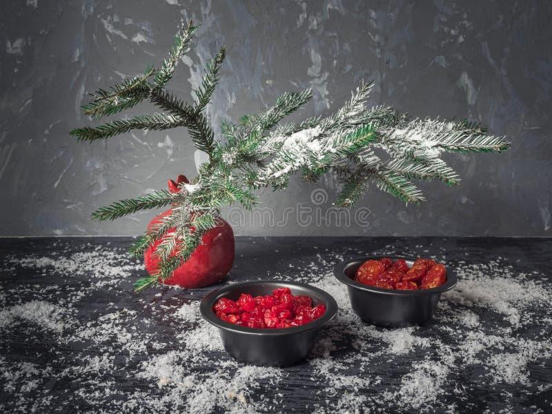 En uppsättning av röda söta torkade frukter i svarta vaser, en röd vas med en granfilial på en mörk bakgrund En spridning av snö  arkivbilder