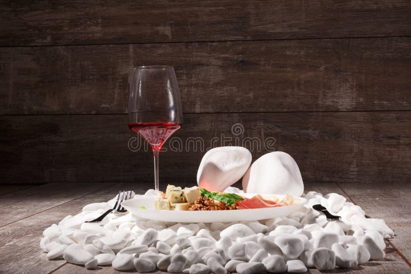 En uppsättning av restaurangläckerhet på en träbakgrund Exponeringsglas av rött vin och aptitretande kött och ost på vit vaggar arkivfoton