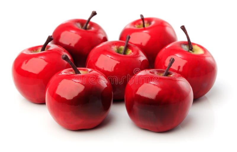 En uppsättning av sju röda plast- äpplen royaltyfri bild