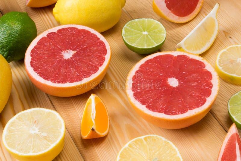 En uppsättning av skivade citrusfrukter ligger tillsammans på ett träbräde arkivbilder
