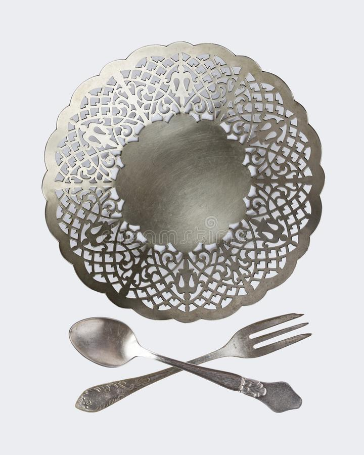 En uppsättning av tappningbordsservis: platta, korsade gafflar och skedar på en vit bakgrund antik silverware retro stil arkivfoto