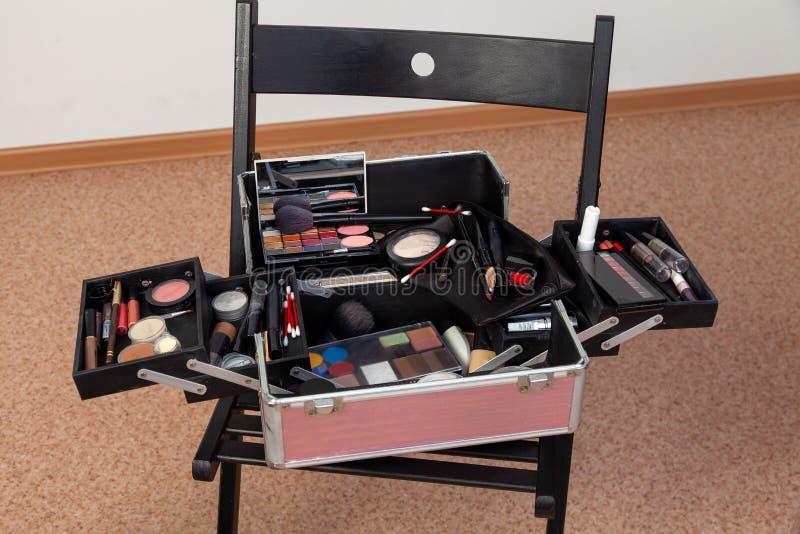 En uppsättning av yrkesmässiga skönhetsmedel i en resväskaask i en öppen form på en stol i en skönhetstudio med många produkter i royaltyfri bild