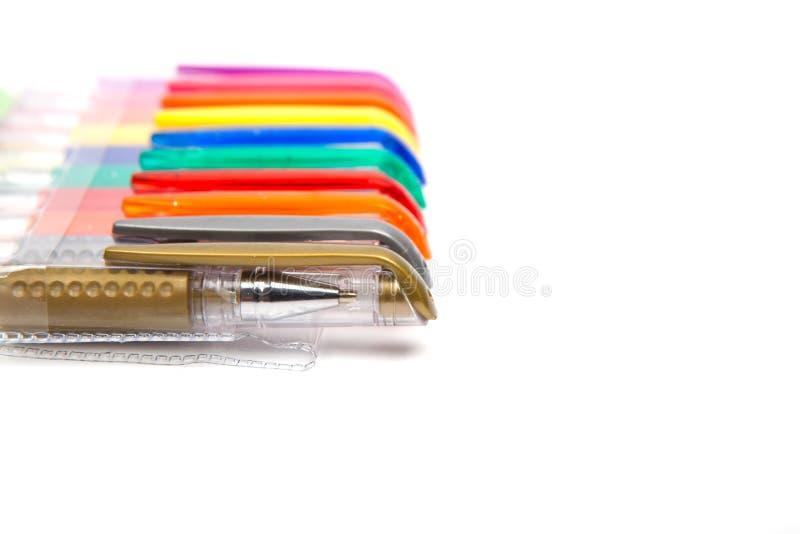 En uppsättning färgade pennor på en vit bakgrund arkivbild