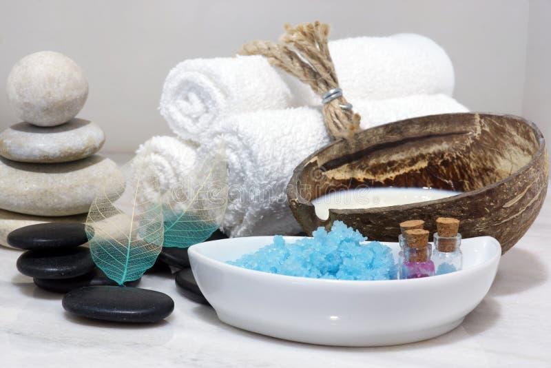 En uppsättning för Spa behandlingar med kokosnöten mjölkar, varma stenar, och blått salt för bad lokaliseras på en vit marmorcoun fotografering för bildbyråer