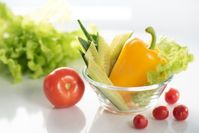 En upps?ttning av nya gr?nsaker p? en vit platta, f?r f?rberedelsen av vegetarisk sallad f?r gr?nsak Bakgrunden ?r vit arkivfoto