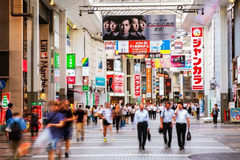 En upptagen shoppa gata i Kumamoto, Japan, med färgglat japanskt bokstavstecken arkivfoto