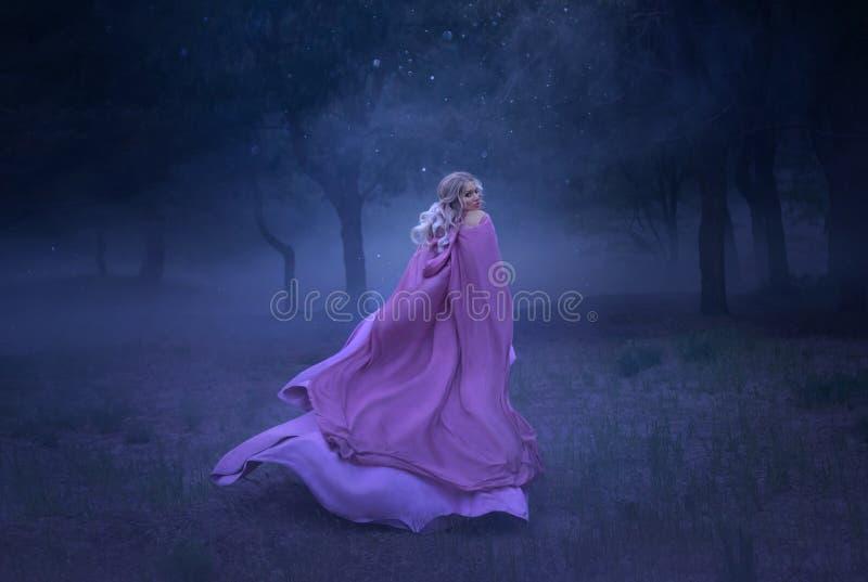 En ursnygg ung älvaprinsessa med blont hår, som flyr i en skog mycket av vit mist som är iklätt ett långt som är dyr arkivbild