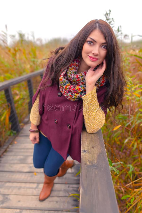 En ursnygg ung kvinna med härligt långt brunt hår som utomhus poserar i ett modesätt Modellen i höstfärger utrustar royaltyfri bild