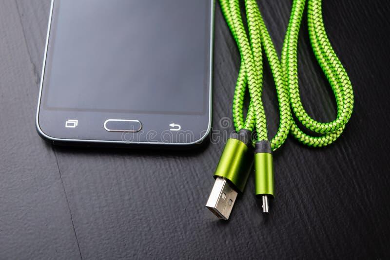 En usb-kabel för uppladdning för dataöverföring och telefon Telefon och tillbehör på tabellen royaltyfri foto