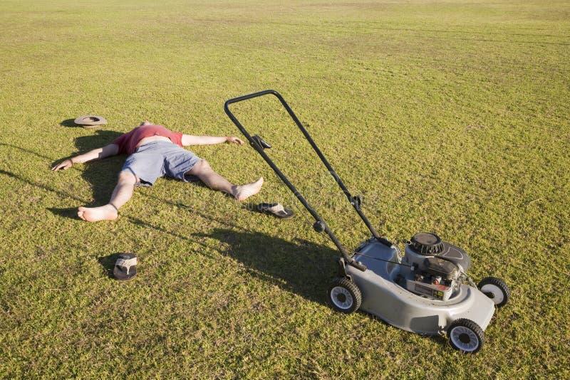 En utmattad gräsmatta som mejar mannen royaltyfri foto