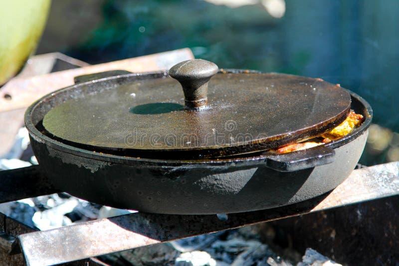 En utomhus- matlagning med gjutjärnstekpannan royaltyfri fotografi