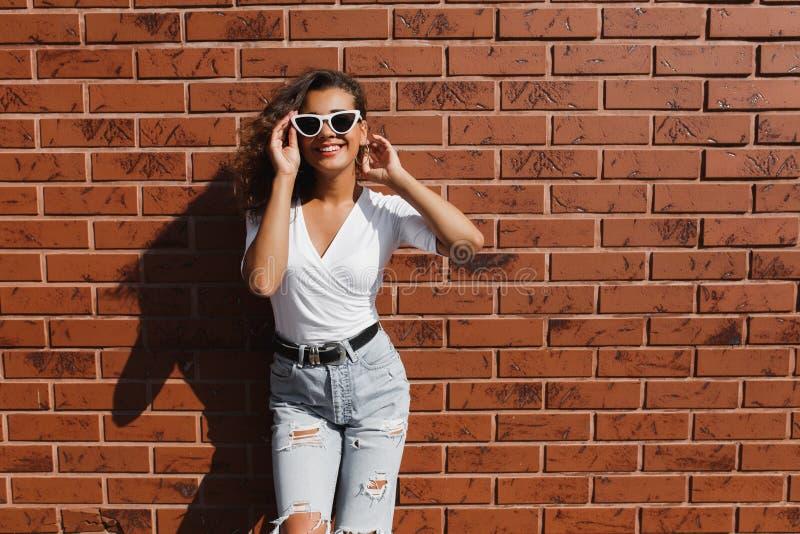 En utomhus- stående av en ung nätt hipsterflicka med lockigt flickahår för lång brunett royaltyfri foto