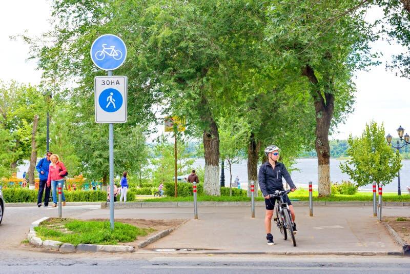 En utrustad cyklist står på trottoaren på en övergångsställe royaltyfria foton