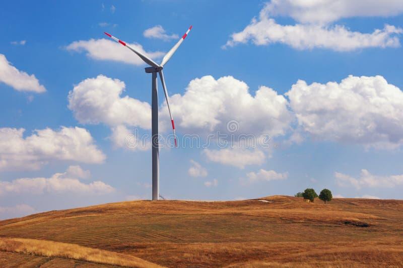 En väderkvarn på bakgrunden av den gula grässlätten och blå himmel Montenegro Niksic, vindkraftväxt i Krnovo royaltyfri foto