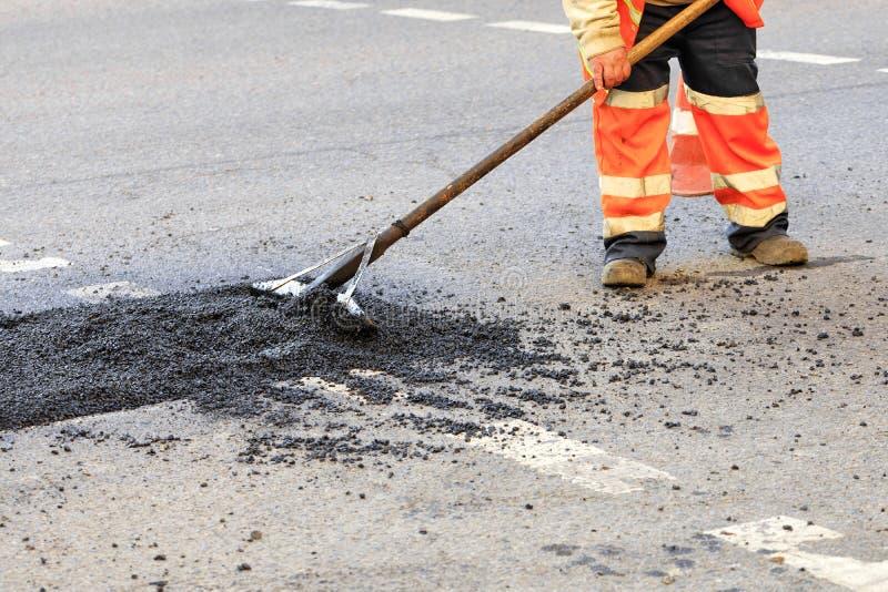 En vägbyggmästare samlar ny asfalt på delen av vägen och jämnar den för reparation i vägkonstruktion arkivfoto