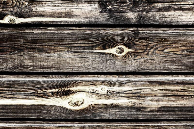 En vägg av gammalt sörjer trätimmer med fnuren som är utbrända i solen arkivfoto