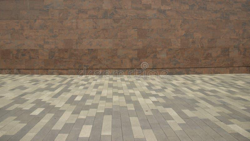 En vägg av marmorerar tegelplattor och ett golv som göras av pavers royaltyfria bilder