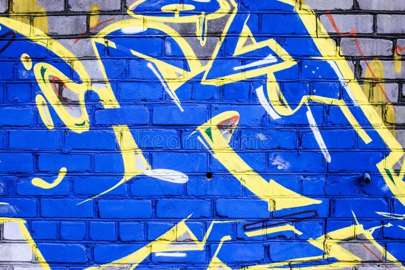 En vägg som vandaliseras med gatagrafittikonst arkivbild