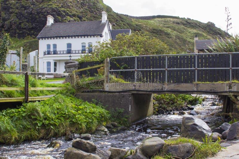 En väl underhållen småhus och trädgård med en flodbortgång under en liten bro arkivbilder