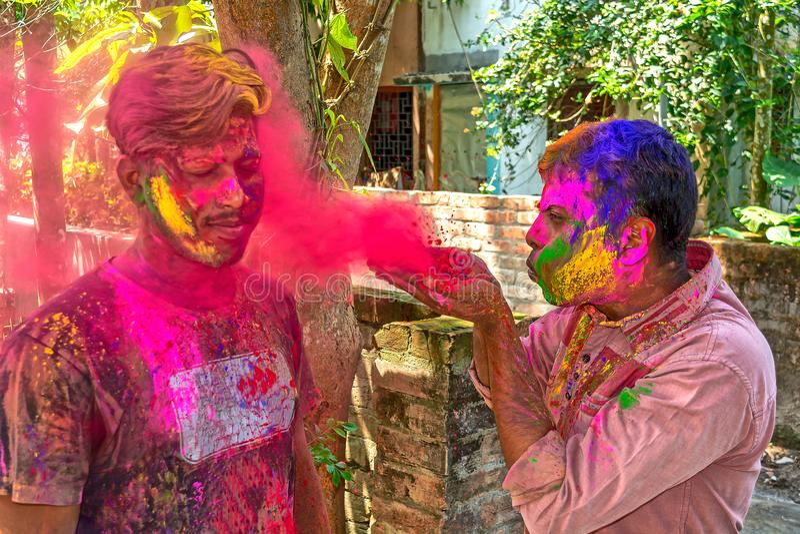 En vän kastar färger till en annan vän under den Holi festivalen i Indien arkivfoton