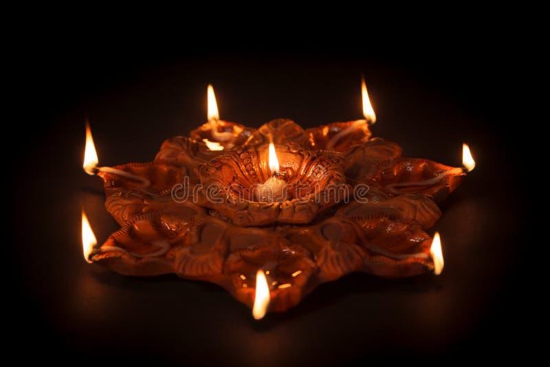 En vända mot jord- olje- lampa påstående sju eller Diya på mörk bakgrund royaltyfria bilder