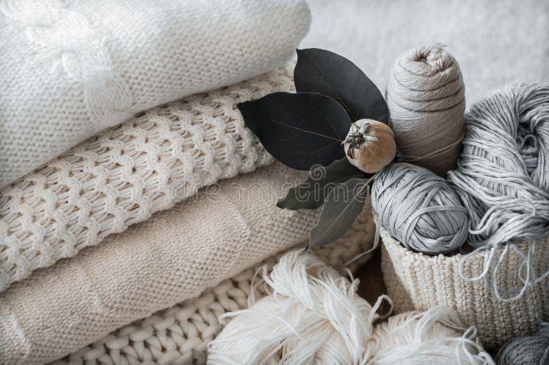 En vävd korg med den vita tråden för att sticka och stickor Vitt tröjor och garn för att sticka closeupen placera text royaltyfri bild