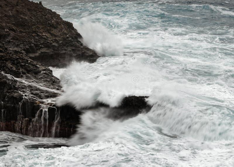 En våg bryter i stormigt väder på en stenig kust fotografering för bildbyråer