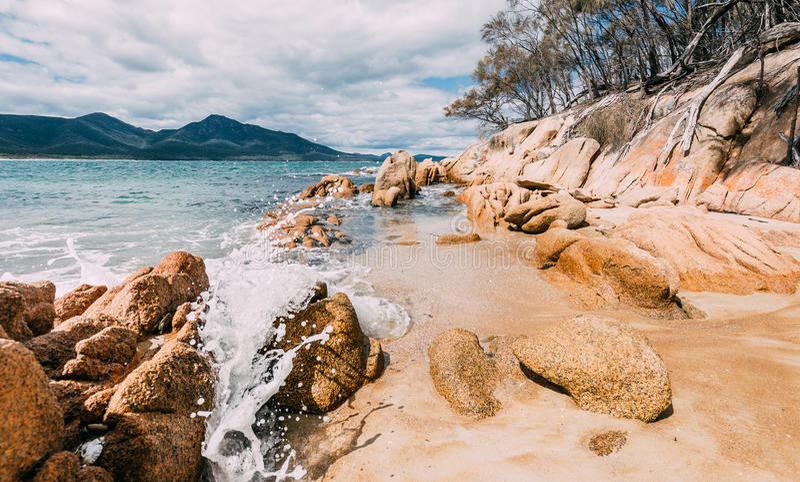 En våg som kraschar på, vaggar i en nationalpark i Tasmanien, med berg i bakgrunden royaltyfria foton