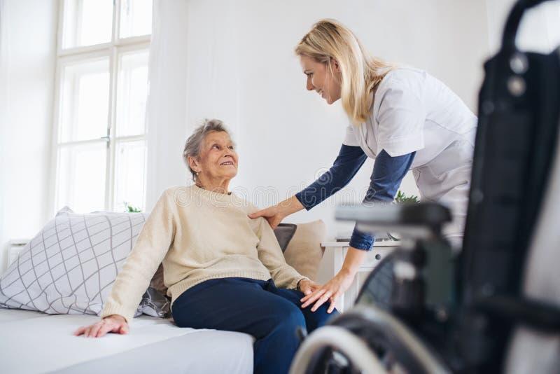 En vård- besökare som talar till en hög kvinna som hemma sitter på säng arkivfoto