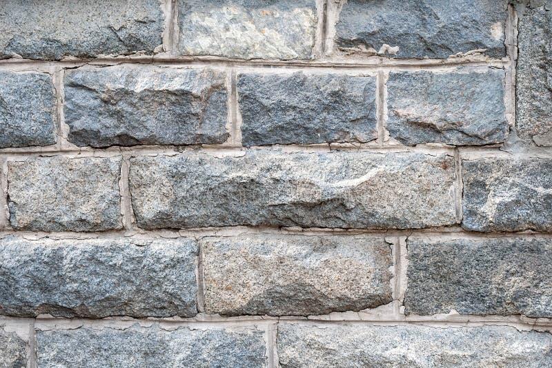 En v?gg av grova granittegelstenar med cementgrout dem emellan royaltyfri foto