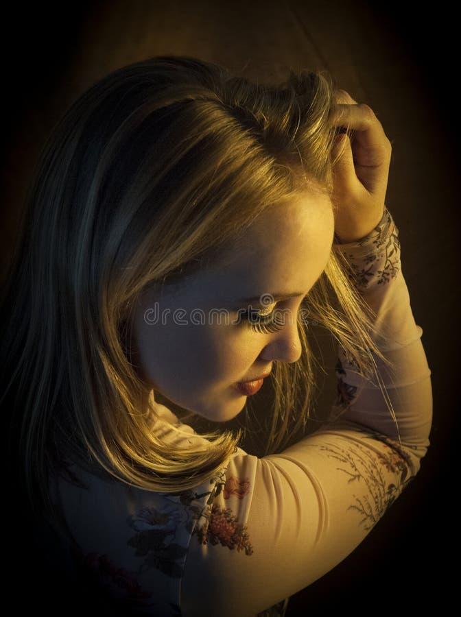 En vacker blond kvinna i varmt gyllene ljus med blända ögon royaltyfri bild