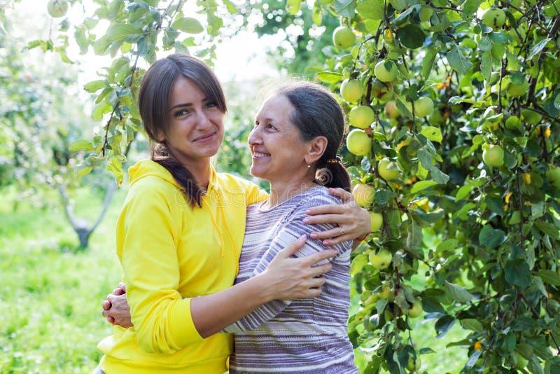 En vacker flicka bredvid mogen mamma i trädgården royaltyfri bild