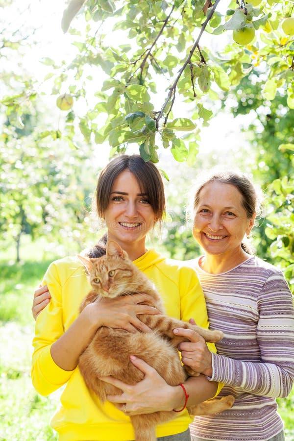 En vacker flicka bredvid mogen mamma i trädgården arkivbild