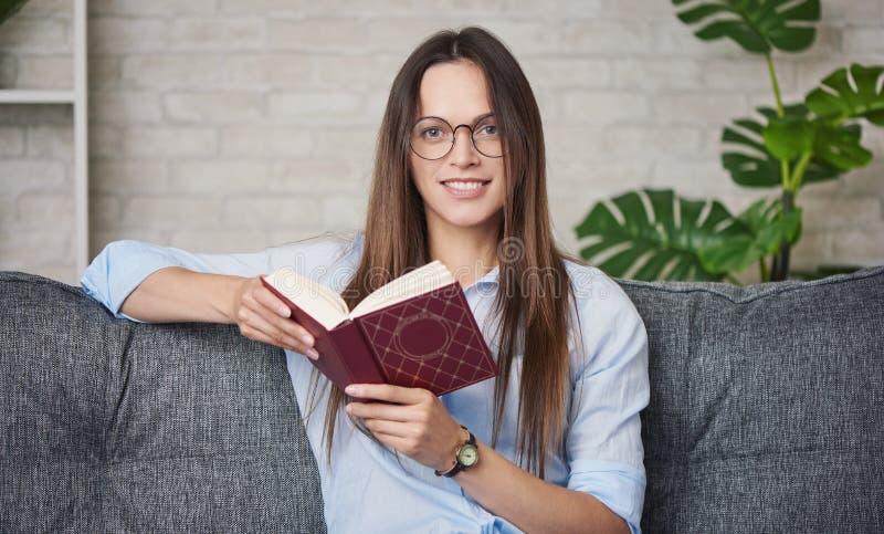 En vacker flicka i ögonglasen läser en bok hemma arkivbild