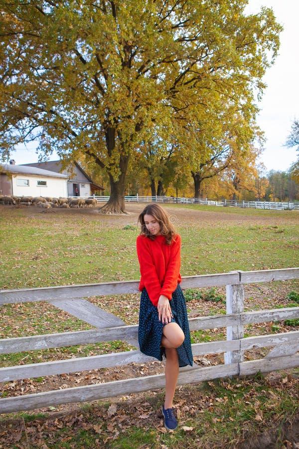 En vacker flicka i en röd tröja står nära ett vitt trästängsel vacker höst arkivbild